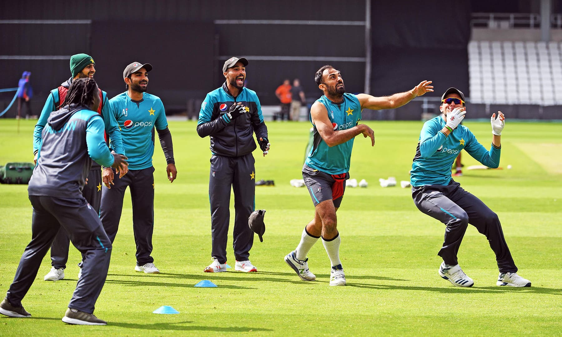 Wahab Riaz (2R) eyes the ball as teammates Shoaib Malik, Asif Ali, Mohammad Amir and Shaheen Shah Afridi look on. — AFP