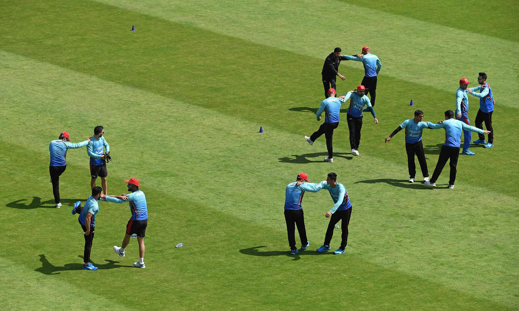 Afghanistan players doing warmup exercises during a training session at Headingly. — AFP