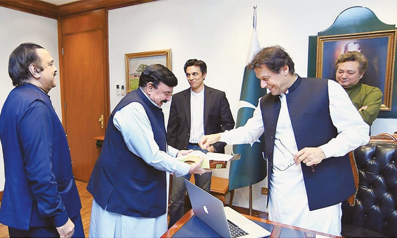 ISLAMABAD: Federal Minister for Railways Sheikh Rashid Ahmed presents sweets to Prime Minister Imran Khan after the Supreme Court gave a verdict in favour of the Ministry of Railways in its legal battle with Royal Palm Country Club.—APP