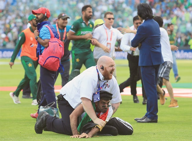 LEEDS: A security official stops a pitch invader after the World Cup match between Pakistan and Afghanistan at Headingley on Saturday. — AFP