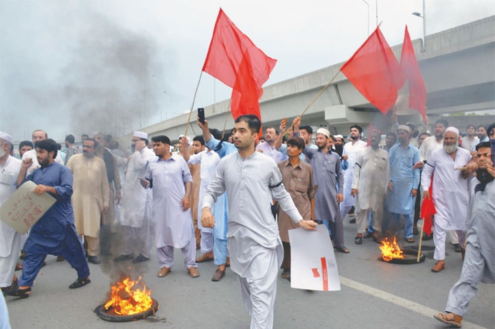 PESHAWAR: Supporters of the Awami National Party block GT Road and burn tyres as they protest against killing of the president of the party's city chapter on Saturday.—PPI