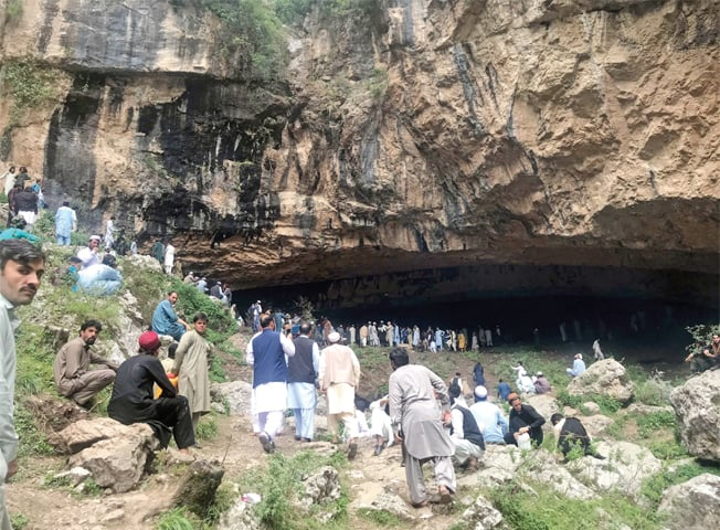 A Swarm of visitors at an ancient cave famous for its healing water near Janatee Cheena in Lar Bagh, Tirah valley. — Dawn