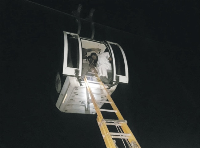 Stranded families being rescued from a cable car in Patriata early Sunday. — Dawn