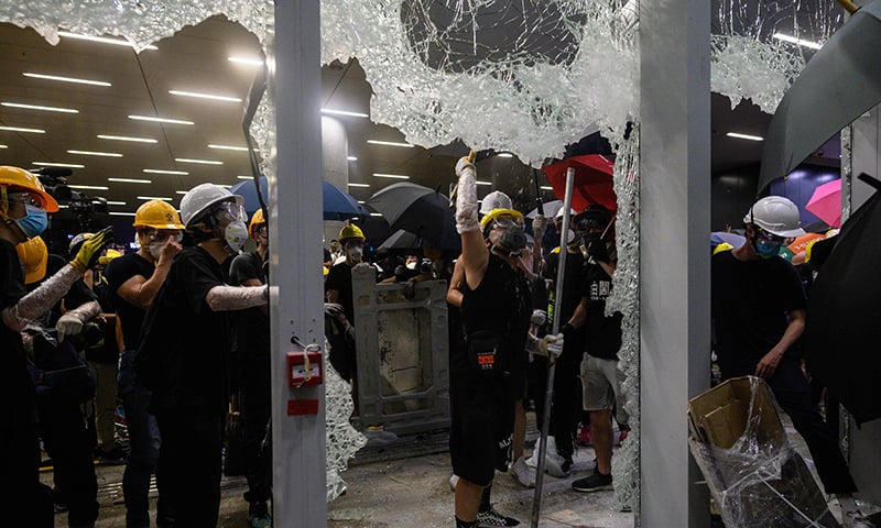 This picture taken on July 1 shows protesters smashing glass doors and windows of the government headquarters in Hong Kong on the 22nd anniversary of the city's handover from Britain to China. — AFP