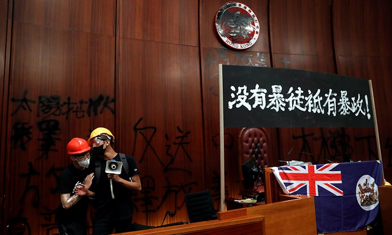 Anti-extradition bill protesters stand next to a colonial flag of Hong Kong and a banner displayed inside a chamber, after protesters broke into the Legislative Council building during the anniversary of Hong Kong's handover to China in Hong Kong, China on July 1. — Reuters