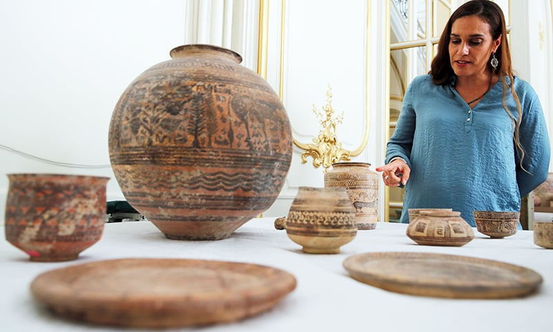 Archaeologist Aurore Didier points to some artifacts amongst the 445 artifacts from the 2nd and 3rd millennium BC. — Reuters