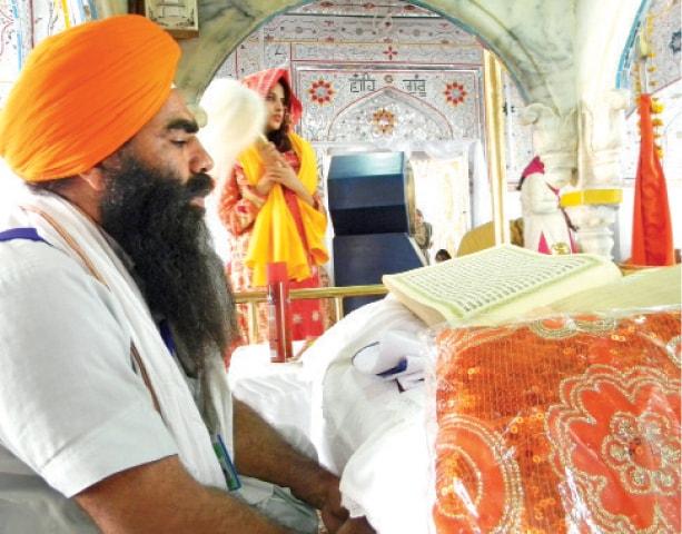 A pilgrim recites the Granth Sahib at Gurdwara Punja Sahib in Hassanabdal on Tuesday. — Dawn