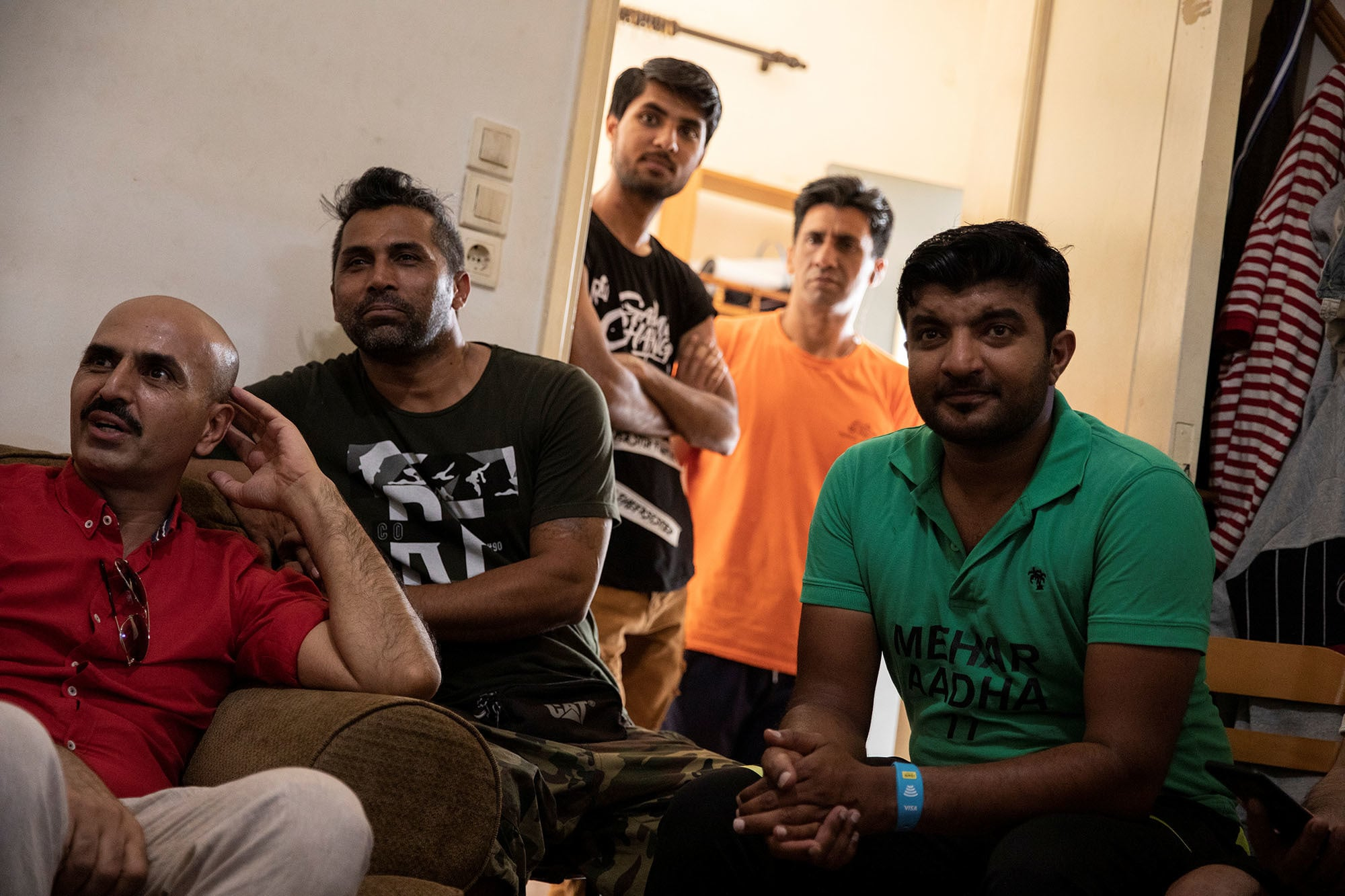 Pakistani street cricketer Awais Mughal, 30, (R) watches his national cricket team's World Cup game against South Africa in an apartment in Athens, Greece on June 23. — Reuters