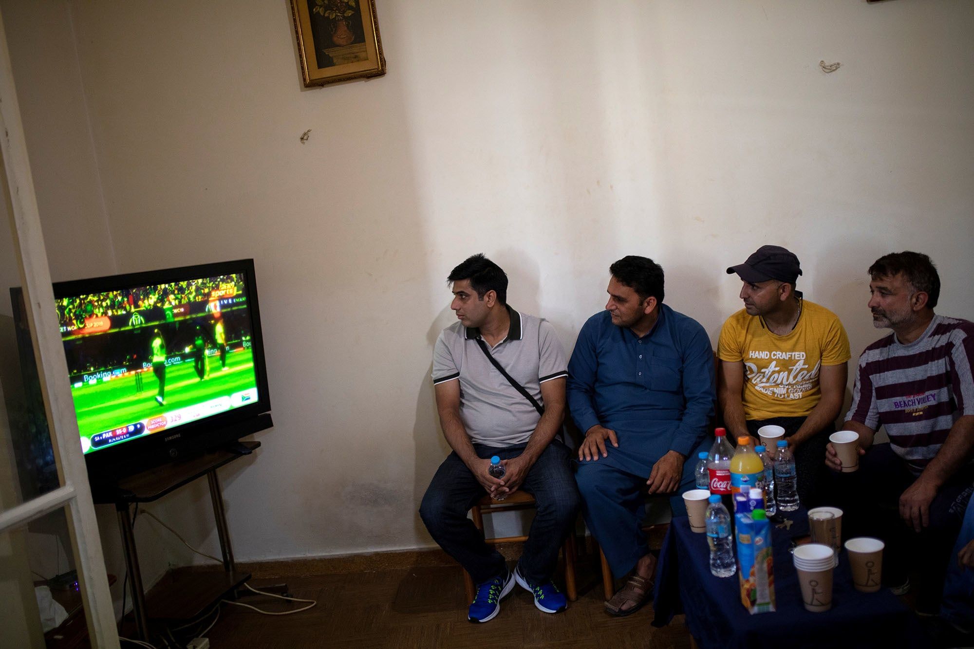 Pakistani men living in Greece watch their national cricket team's World Cup game against South Africa in an apartment in Athens, Greece on June 23. — Reuters