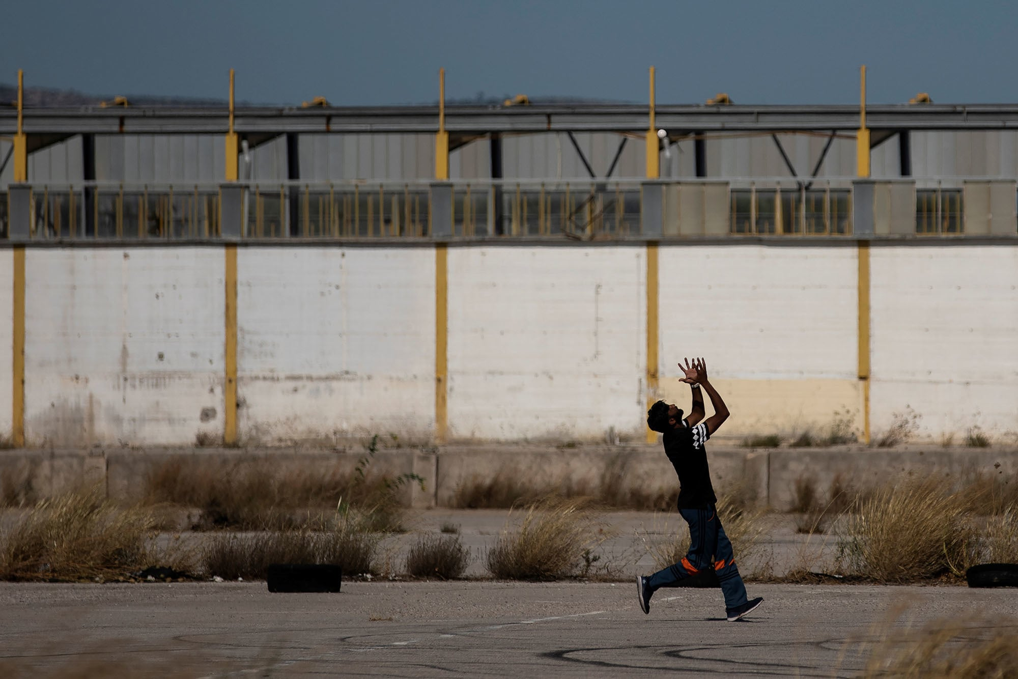 A Pakistani man living in Greece tries to catch the ball during a tape-ball cricket game in a disused parking lot for trucks in an industrial area in Elefsina, Greece on June 30. — Reuters