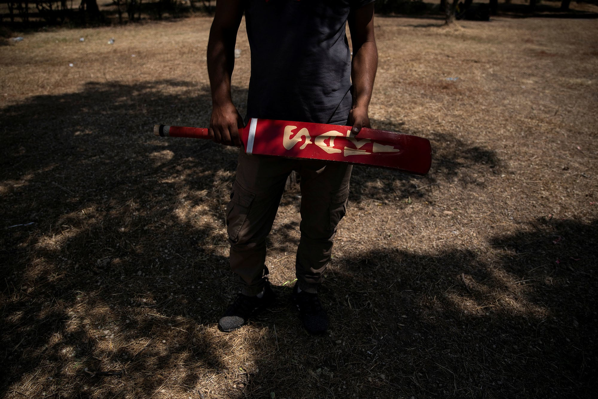 A Pakistani man living in Greece holds a bat before a tape-ball cricket game in a park in the Agioi Anargyroi suburb in Athens, Greece on June 23. — Reuters