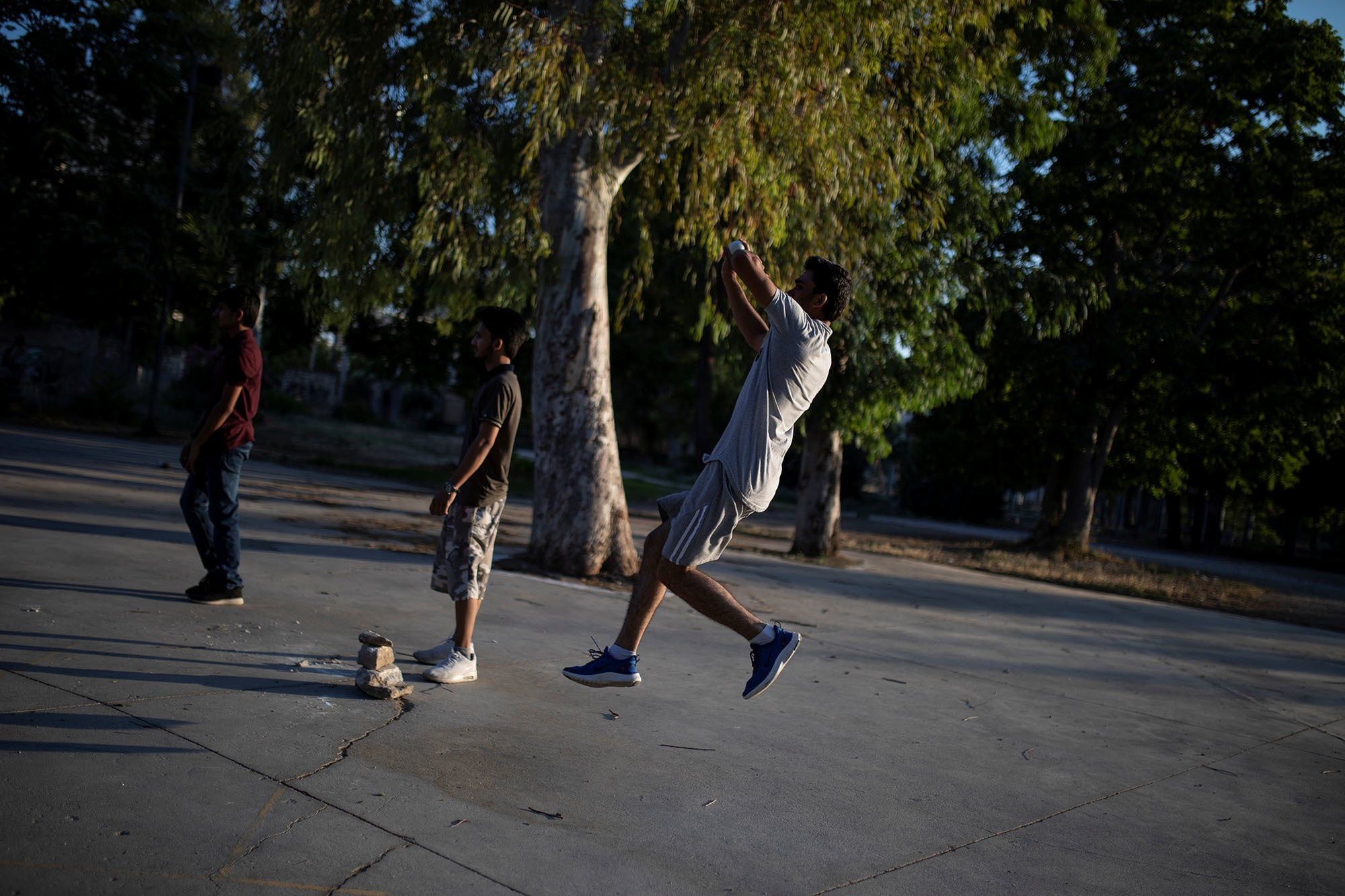 A Pakistani man living in Greece bawls a ball during a tape-ball cricket game in a parking lot in the Tavros neighbourhood in Athens, Greece on June 29, 2019. — Reuters