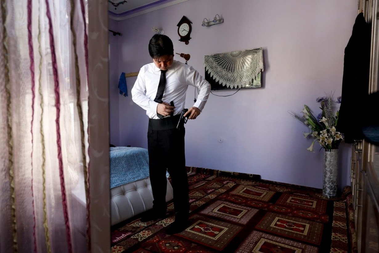 Sardar Sahil sports his licensed gun as he gets ready to leave for office, at his home. ─ Reuters