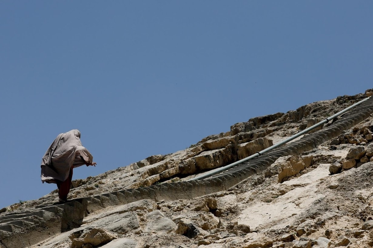 A woman ascends a flight of stairs as she walks home on a hilltop in Mariabad. ─ Reuters