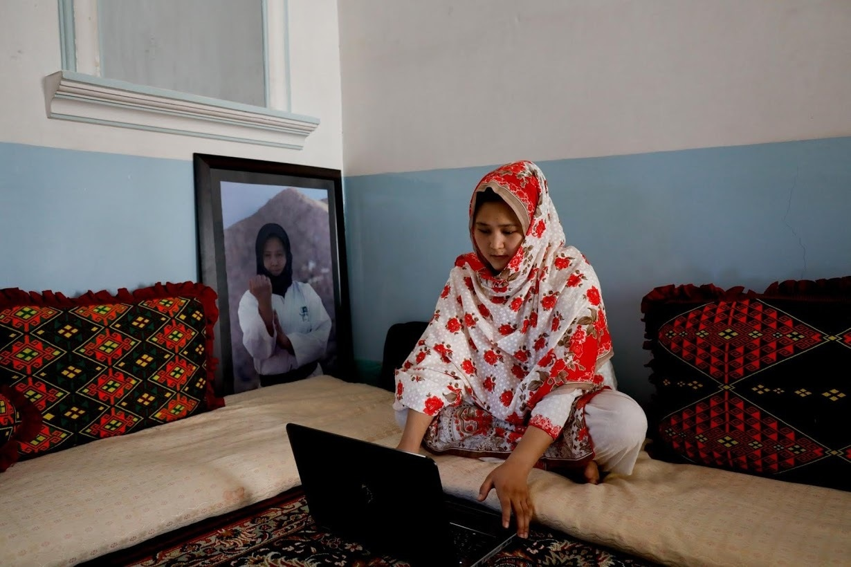 Nargis Hazara works on her computer as she sits beside her portrait at her home. ─ Reuters