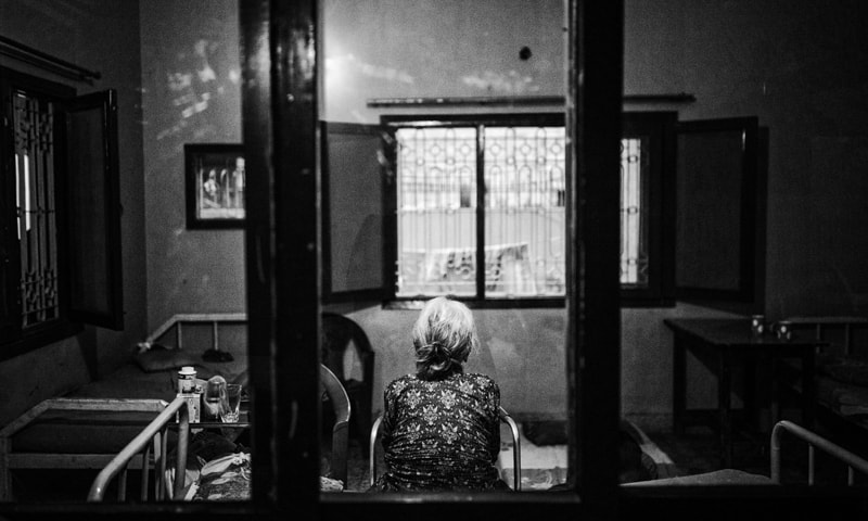 An elderly woman looks out the window of her room in an old people's home | Mohammad Ali / White Star