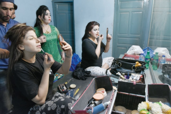 Actors get ready for the play in the makeup room.