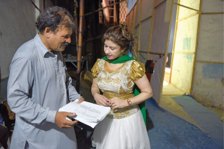 The drama's director discusses a scene with a stage actor.