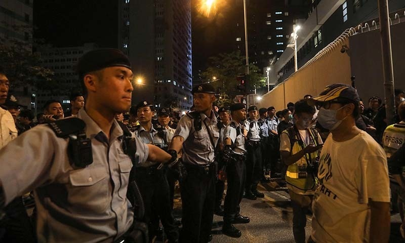 Policemen hold hands to line up and surround protesters during a demonstration in the north-western district of Tuen Mun, near the border with the Chinese city of Shenzhen, in Hong Kong on July 6. — AFP