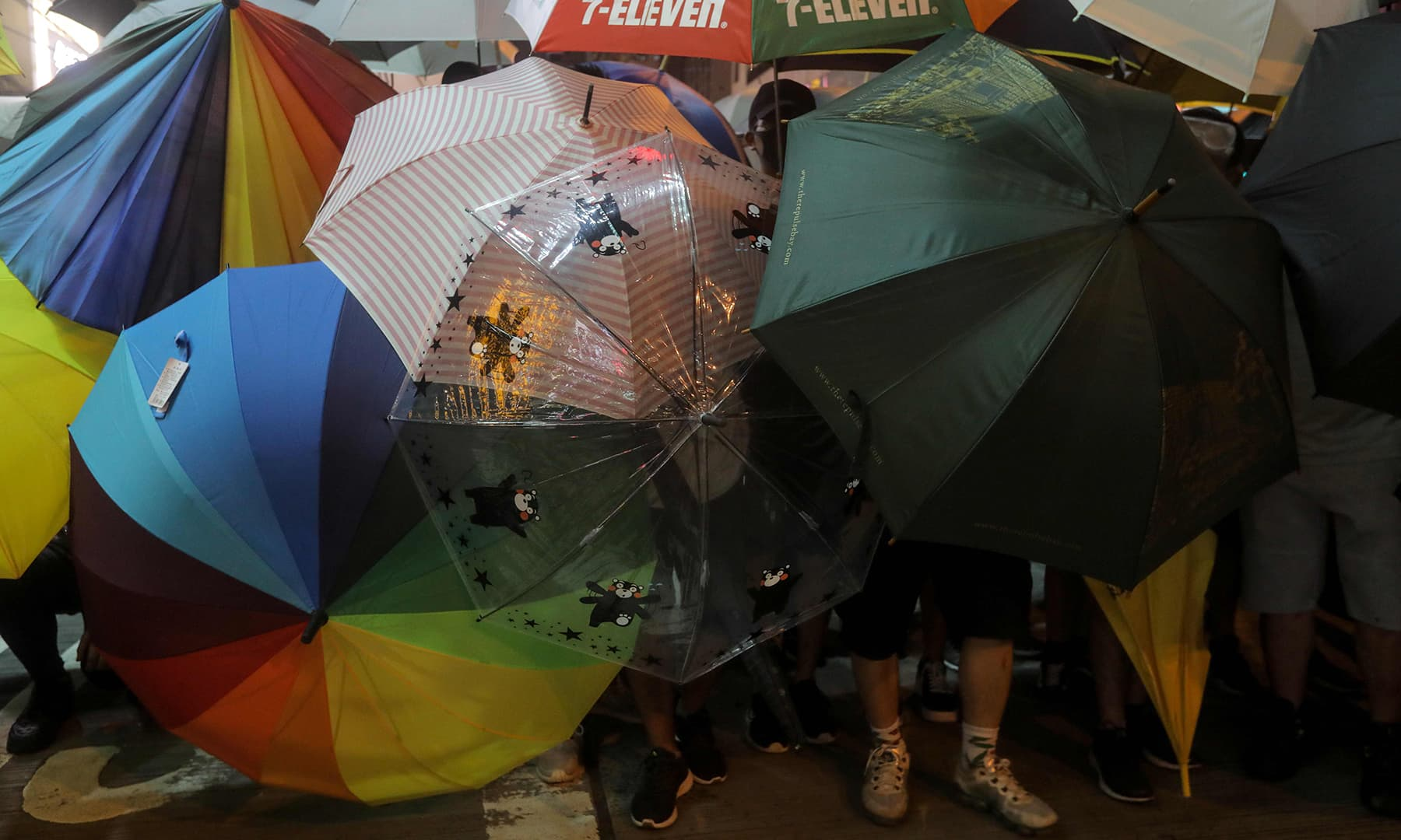 Protesters carry umbrellas to protect themselves as they face the police. — AFP