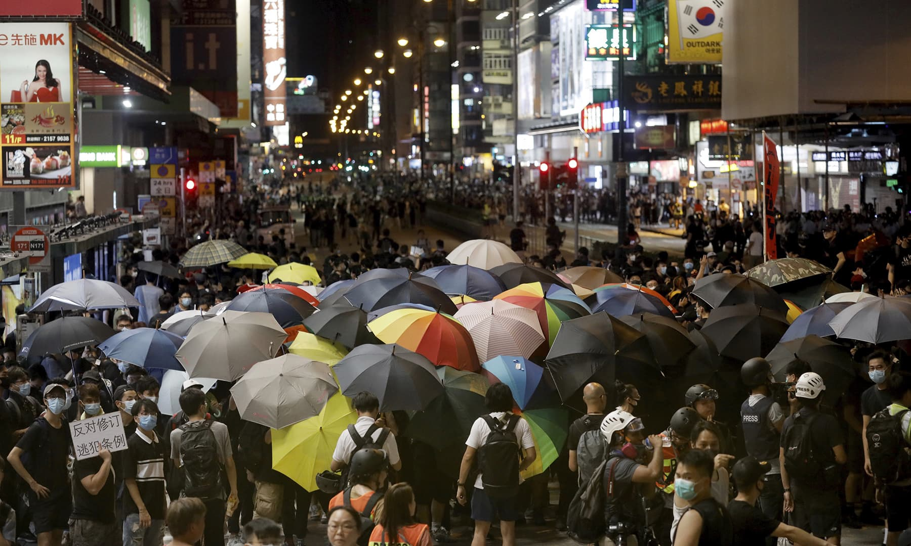 Protesters with umbrellas prepare to face-off police in anti-riot gear in Hong Kong on Sunday, July 7. — AP