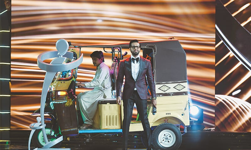 ONE of the hosts, Fahad Mustafa, makes his entrance in an auto rickshaw on stage during the ceremony held at the Expo Centre on Sunday evening.—Faisal Farooqui