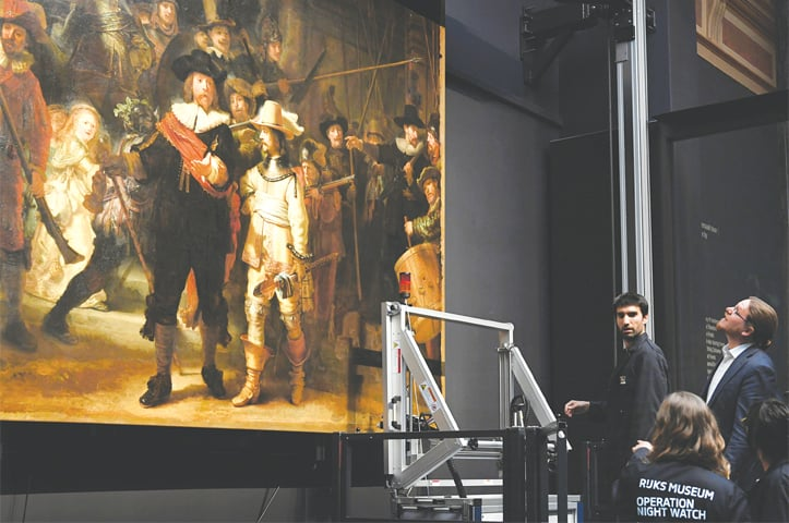 Restorers prepare Rembrandt's famous painting, The Night Watch, protected by a glass barrier, for restoration at Rijksmuseum in Amsterdam, the Netherlands, on Monday.—Reuters