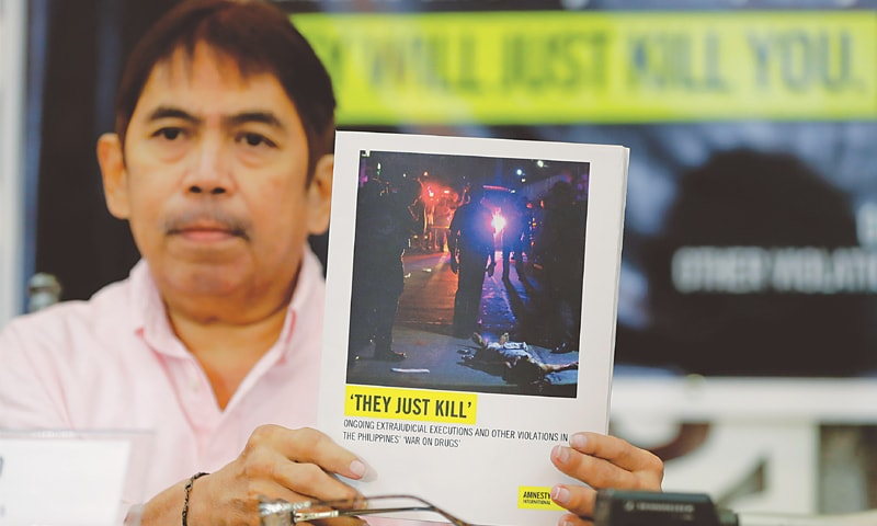 Manila: Butch Olano, Amnesty International's representative in the Philippines, holds a copy of the report during a news conference on Monday.—AP