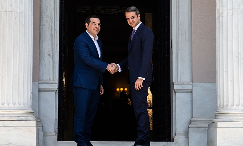 Newly-appointed Greek Prime Minister Kyriakos Mitsotakis (R) shakes hands with former prime minister Alexis Tsipras at the Maximos Mansion in Athens, on July 8. — AFP