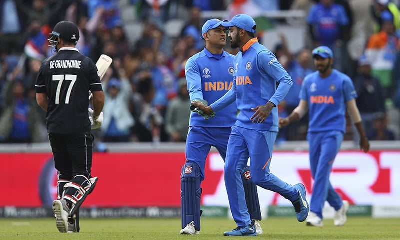 India's Mahendra Singh Dhoni, second left, celebrates after taking a catch to dismiss New Zealand's Colin de Grandhomme during the Cricket World Cup semifinal match between India and New Zealand at Old Trafford on July 9. — AP