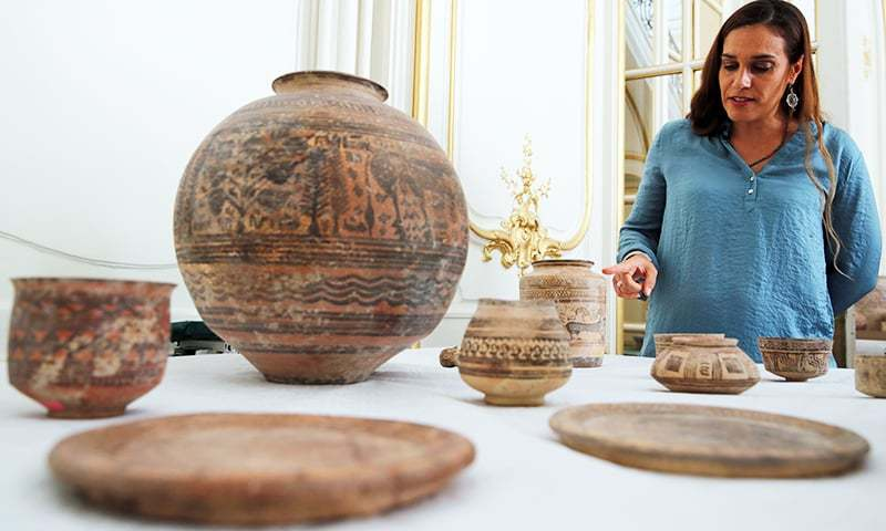 Archaeologist Aurore Didier points to some artefacts amongst the 445 artefacts from the 2nd and 3rd millennium BC which were seized by French customs between 2006 and 2007, before being returned by French authorities to Pakistan, during a ceremony at the Embassy of Pakistan in Paris, France, July 2, 2019.  Photo: File/Reuters