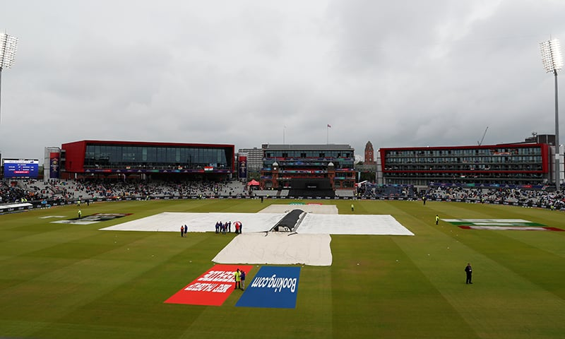 Groundstaff covers pitches at Old Trafford where the World Cup semi-final between India and New Zealand has been interrupted by rain. — Reuters