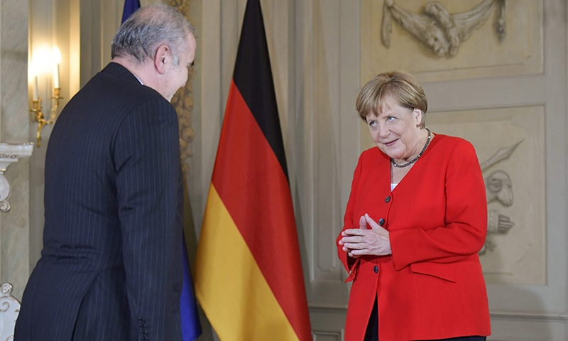 German Chancellor Merkel welcomes Ali Akbar Dabiran, Iran's representative to Germany, during a reception of the diplomatic corps at the German governmental guest house in Meseberg, northeastern Germany on July 9. — AFP