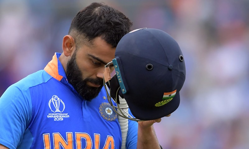 India's captain Virat Kohli leaves the pitch after losing his wicket for 1 run during the 2019 Cricket World Cup first semi-final between New Zealand and India at Old Trafford in Manchester northwest England on July 10. — AFP
