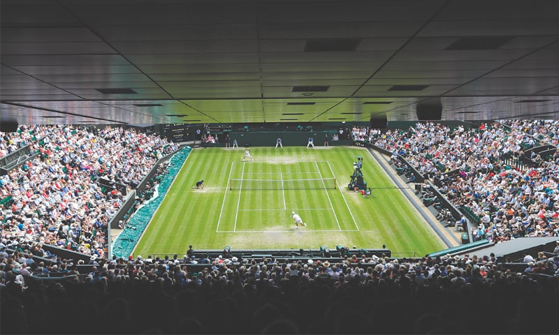 LONDON: Novak Djokovic of Serbia (bottom) serves to Belgium's David Goffin during their Wimbledon quarter-final on Wednesday. — AP