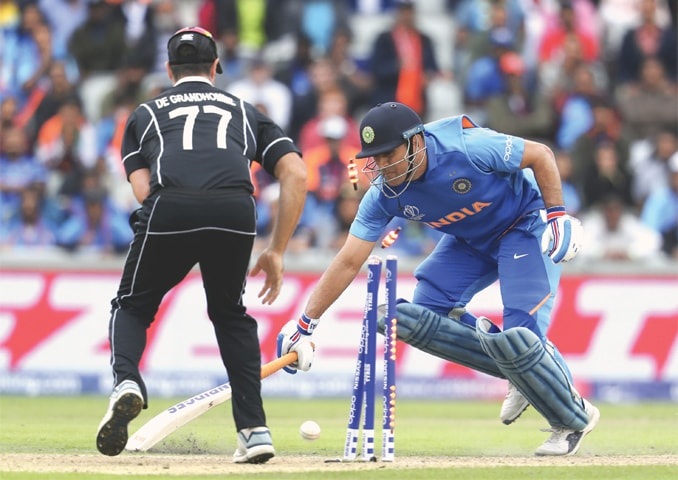 IN what proved to be the turning point of the game, Indian batsman M.S. Dhoni gets run out, as New Zealand's Colin de Grandhomme looks on, during the first semi-final at Old Trafford on Wednesday.—AP
