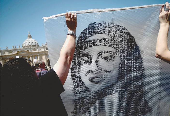 IN this file photo taken on May 27, 2012, demonstrators hold a poster of Emanuela Orlandi during Pope Benedict XVI's prayer in St. Peter's Square. The Vatican has decided to open an internal probe into the case of Emanuela Orlandi, a teenager who disappeared in 1983 in one of Italy's darkest mysteries.—AFP