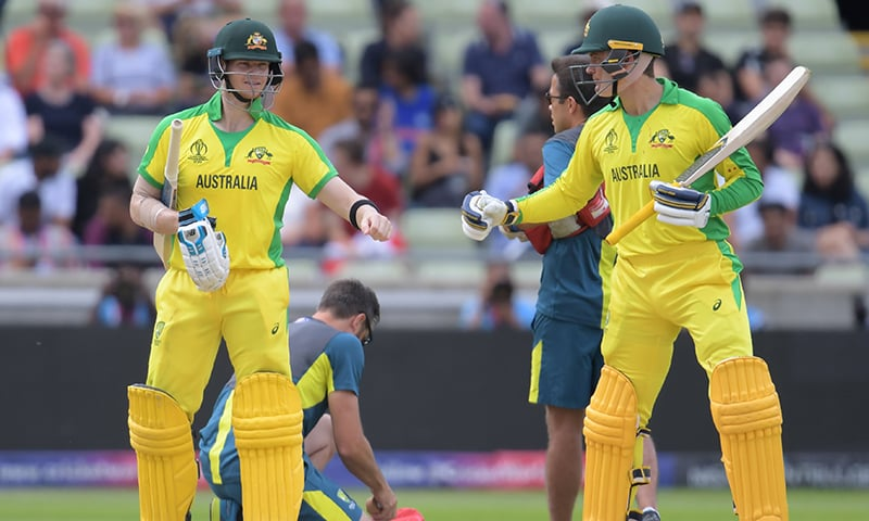 Australia's Alex Carey (R) touches gloves with teammate Steve Smith as he walks back to the crease to resume batting after receiving continued medical attention after he was hit by a bouncer by England's Jofra Archer during the World Cup second semi-final between England and Australia at Edgbaston on July 11. — AFP