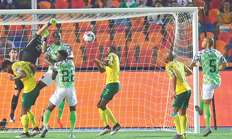 CAIRO: Nigeria's William Ekong (R) gets in position before scoring during the African Cup of Nations quarter-final against South Africa at the Cairo International Stadium.—AFP