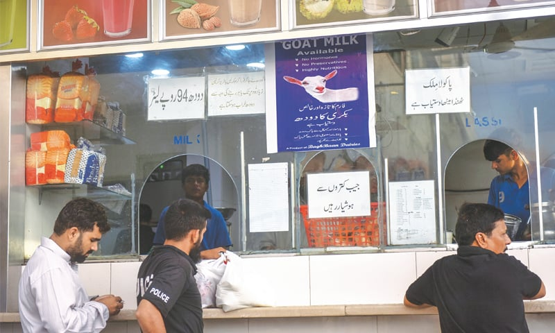 PEOPLE buy milk from a shop in DHA on Thursday. — White Star