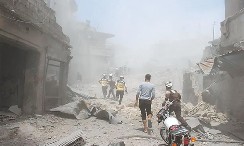 Jisr al-Shughur: Syrian civil defence workers, also known as White Helmets, rush to a street that was hit by Syrian government's air strikes on Thursday. — AP