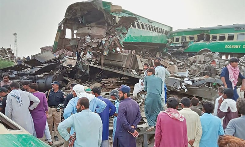 Local residents gather around the wreckage of carriages at the site where two trains collided in Rahim Yar Khan district on Thursday. — AFP