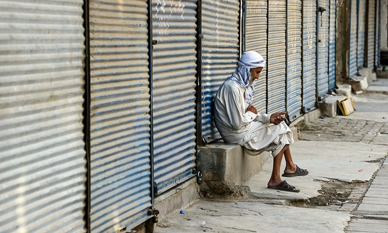 An elderly man sits at a shuttered market during a traders countrywide strike against the price hike, in Peshawar on July 13. — AFP
