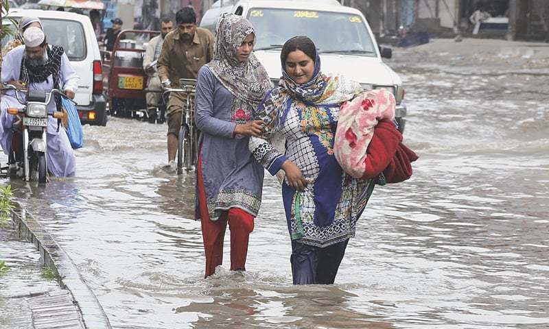In this file photo, people wade through a flooded street after heavy rains in Lahore. — AP