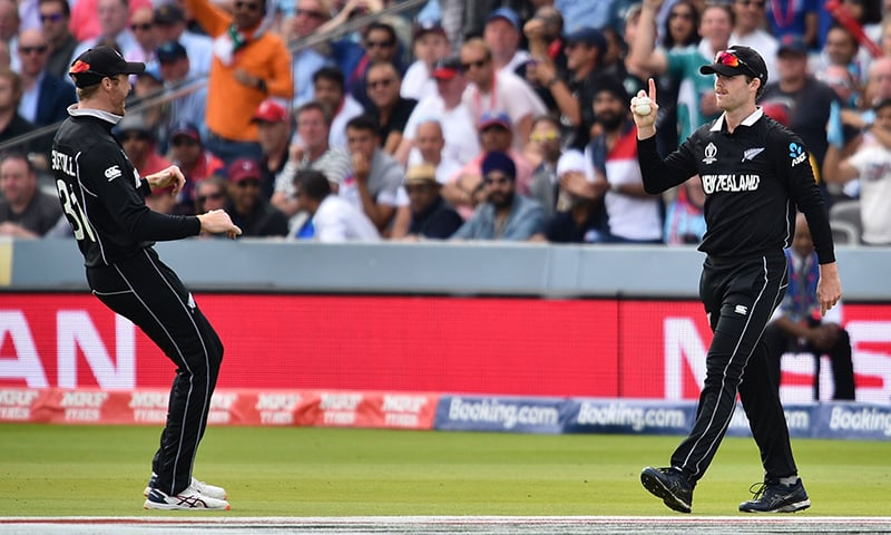 New Zealand's Lockie Ferguson (R) celebrates after catching the ball to take the wicket of England's captain Eoin Morgan for nine runs during the 2019 Cricket World Cup final between England and New Zealand at Lord's Cricket Ground in London on July 14. — AFP
