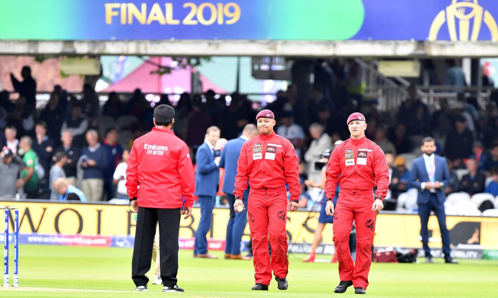 برٹش آرمی کی پراشوٹ رجمنٹ کے جوان پیرا شوٹ کے ذریعے ورلڈ کپ فائنل کی گیند میدان میں لانے کے بعد پاکستانی امپائر علیم ڈار کو دینے کے لیے آ رہے ہیں— اے ایف پی