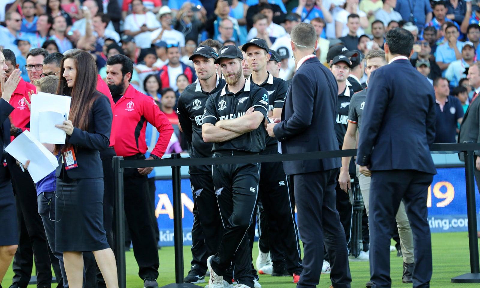 ورلڈ کپ فائنل میں ناکامی پر نیوزی لینڈ کے کھلاڑی افسردہ کھڑے ہیں— فوٹو: رائٹرز