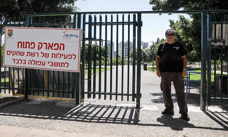 "An Israeli security guard stands next to a sign reading in Hebrew ""the park is open for activity by Reshet (Group) Shehakim and to residents of Afula only"", at the gate of a municipal park in the northern Israeli city of Afula on July 14. — AFP"