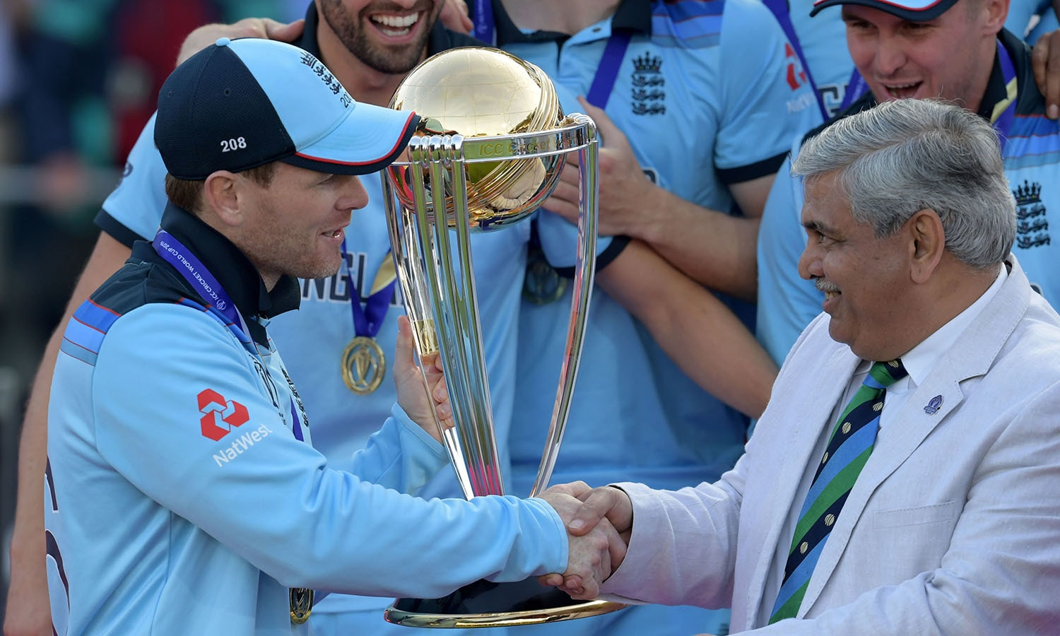 England's captain Eoin Morgan shakes hands with ICC Chairman Shashank Manohar as he lifts the World Cup trophy. — AFP