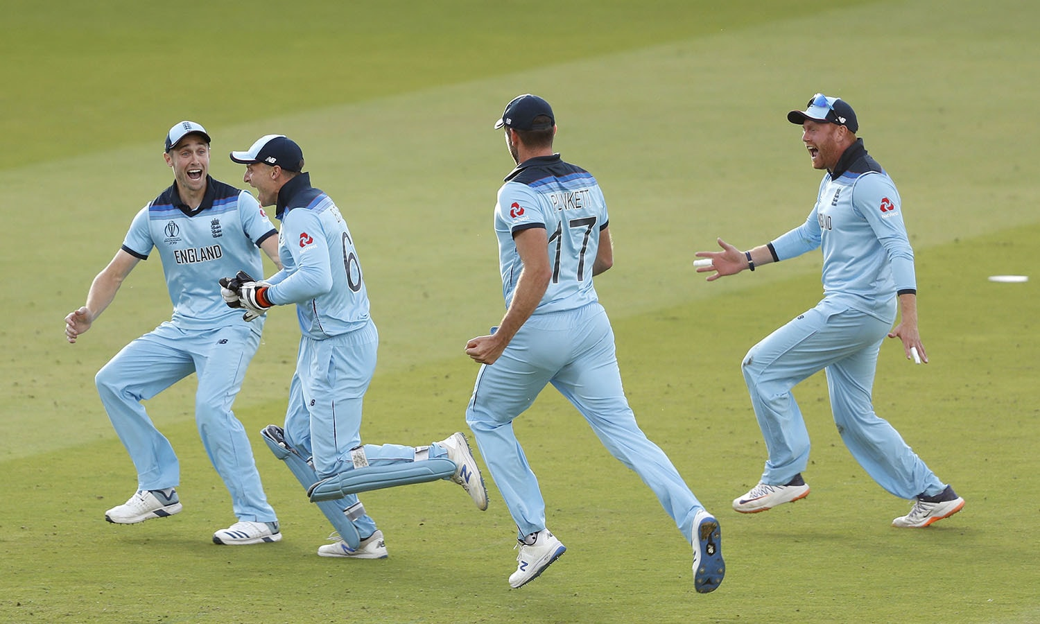 England celebrates after running out New Zealand's Martin Guptill to win the Cricket World Cup. — AP